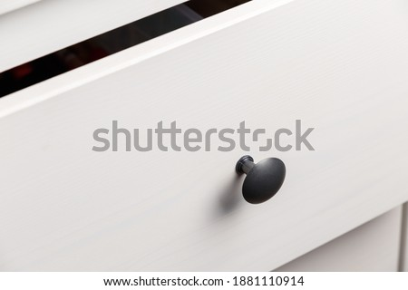 Black handle on white wooden chest of drawers. Minimalism. Minimal concept. Close-up. The texture of natural wood Сток-фото ©