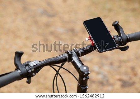 Black handlebar of sport bicycle over forest road background, having smartphone attached to right side, movement along road, gps navigator, going according to online map. Orientation concept. #1562482912