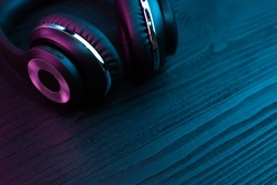 Black headphone on dark wooden background. Stylish wireless headset in neon light.