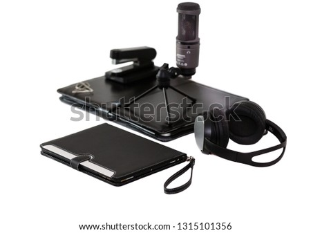 Black headphones, microphone, tablet, laptop in a black leather cover and stapler on a white background