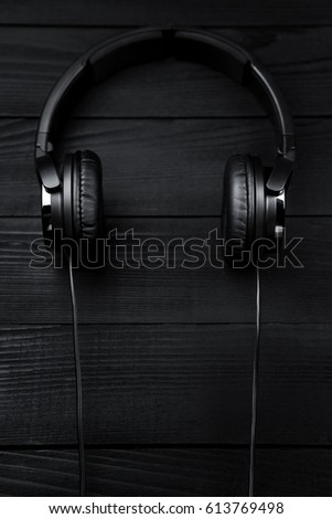 Black headphones on black wooden dark background #613769498