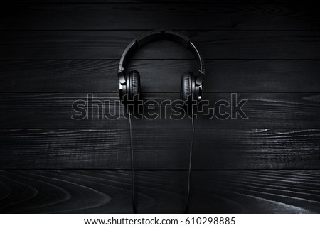 Black headphones on brown wooden dark background