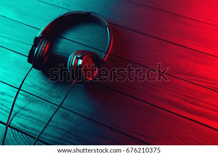 Black headphones on dark wooden background. Vintage style #676210375