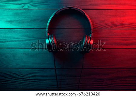 Black headphones on dark wooden background. Vintage style #676210420