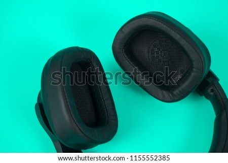 Black Headphons on aqua color background with copyspace. #1155552385