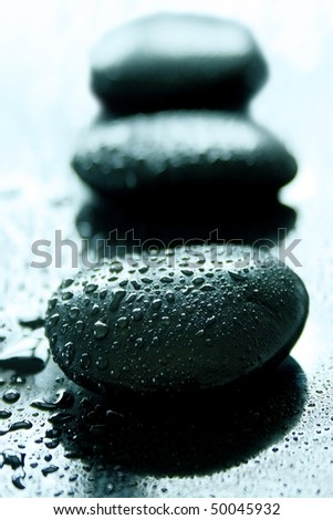 Black healing stones on a wet black surface