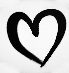 Black heart on white wall background. dark heart painted on gray  wal.l close-up image.