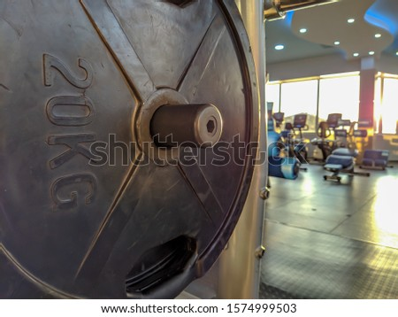 Black heavy metal steel of 20 kilograms for weight lifting inside a gym with many different equipment for strength and endurance training