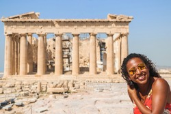 Black Hipster traveler smiling sitting in ruins, on the background of the Parthenon on the Acropolis of Athens, Greece. Vacation woman enjoying the visit in Athens