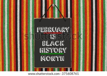 Black History Month Blackboard hanging on Striped Pattern Background #375608761