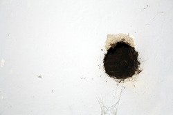 black hole in in white wall as a background