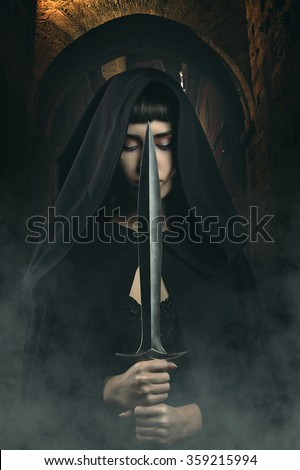 Stock Photo Black hooded thief with knife in dark village alley . Fantasy and legend