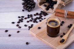 black hot espresso coffee shot in glass with coffee beans, wooden spoon and bag. low fat coffee no sugar.