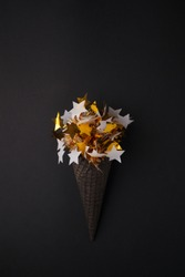 Black Ice Cream Cone with white gold star garland on black background, monochrome party minimal closeup