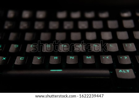 black illuminated keyboard with green light, dark tone, selective focus