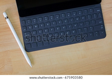 Black iPad pro tablet computer connecting on portable keyboard next to white pencil pen on wooden background with copyspace