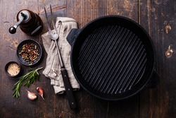 Black iron empty grill pan, seasonings and meat fork on wooden texture background