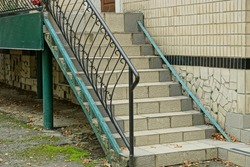 black iron handrails with a forged pattern on the stairs with gray concrete steps against a brown wall