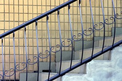 black iron handrails with a forged pattern on the stairs with white concrete steps against a brown wall