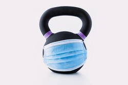 Black iron kettlebell with blue surgical mask across on white background