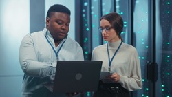 Black IT administrator instructing young female intern showing multiple rack server cabinets coworking in high tech server room of data center complex.