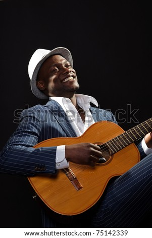 Black jazz musician wearing suit and grey hat playing guitar.