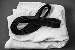 Black judo, aikido or karate belt on white judo gi