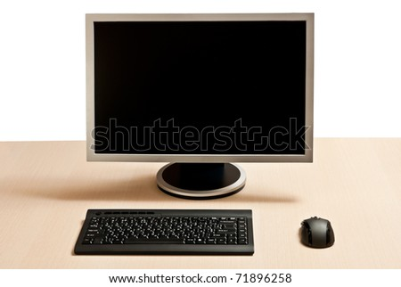 Black keyboard, mouse and monitor on a wood desk.