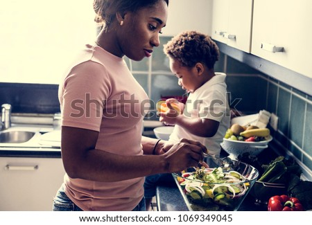 Black kid with mom in the kitchen #1069349045