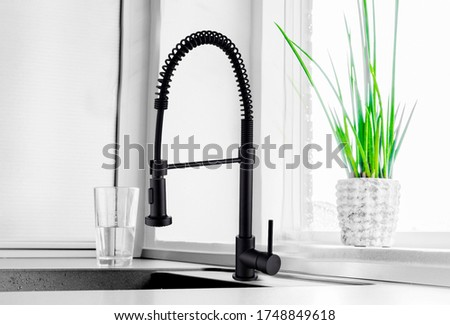 Black kitchen faucet on the silver sink near the glass of water  Foto d'archivio ©