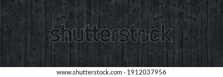 Black knotty wooden board wide texture. Dark grey wood plank panorama. Gloomy grunge panoramic widescreen background Stock photo ©