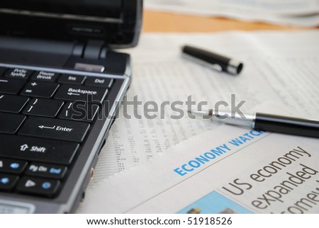 Black laptop and stock figures. Camera focus on newspaper. For concepts such as business and finance, internet and technology, and stock analysis and financial investment. - stock photo