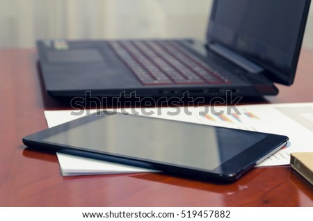 Black laptop and tablet on wood table - Shutterstock ID 519457882