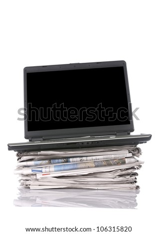 Black laptop with stacking newspaper isolated on white background. You can put your message on the screen