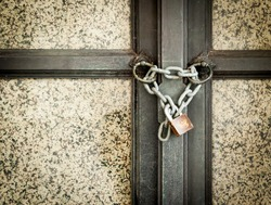 black large door closed with a chain and a lock