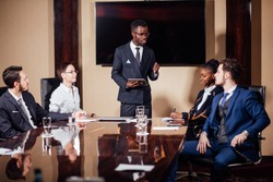 black leader of the business people giving a speech in a conference room.