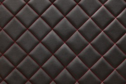 Black  leather background and texture stitched with red diamond-shaped threads as a pattern for the interior of the vehicle's interior waist in the vehicle maintenance workshop.