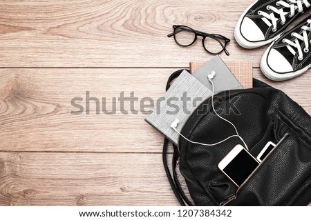 Black leather backpack with books, glasses, phone, player with headphones and sneakers on a wooden background. Stock foto ©