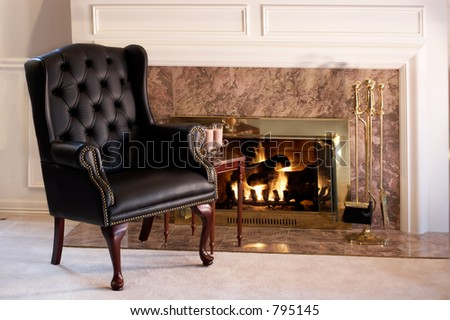 Black leather chair by the fire