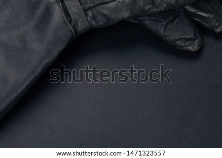 Black leather glove on leather desk