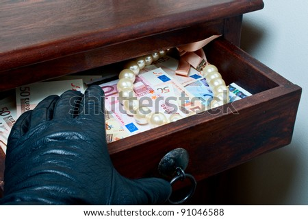 Black leather glove reaching money euro and pearls in drawer