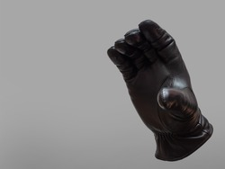 black leather glove shows open mouth gesture. isolated neutral background. copy space