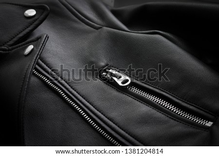 Black leather jacket. The texture of the skin in clothing. Clothing accessories, rivets, buttons, zipper. Sewing leather clothes #1381204814