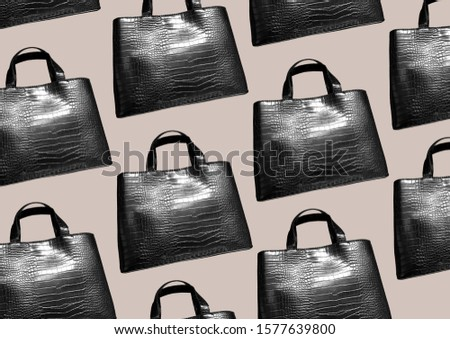 Black leather mock croc tote bag isolated on brown background. Woman elegant handbag with two handles in a showcase. Fashion women accessories. Fashion concept. Pattern