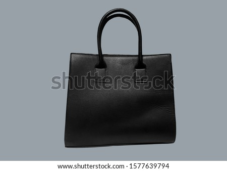 Black leather mock tote bag isolated on blue background. Woman elegant handbag with two handles in a showcase. Fashion women accessories. Fashion concept. Pattern