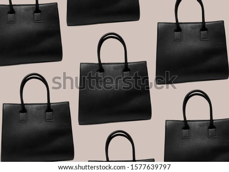 Black leather mock tote bag isolated on brown background. Woman elegant handbag with two handles in a showcase. Fashion women accessories. Fashion concept. Pattern