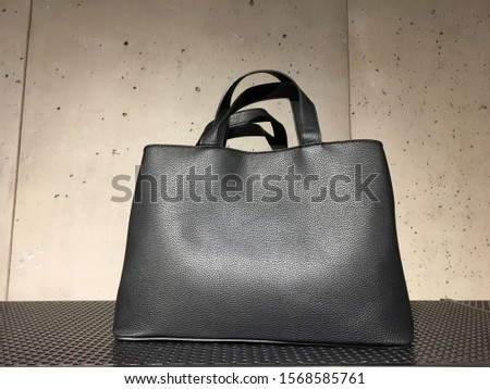 Black leather mock tote bag on shelf. Woman elegant handbag with two handles in a showcase of a luxury store on a concrete background. Fashion women accessories. Fashion concept