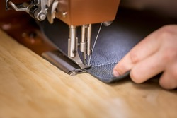 Black leather on industrial sewing machine showing white stitch