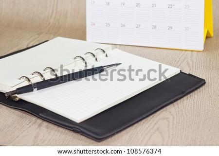 Black leather organizer and pencil and desktop Calendar on wood background