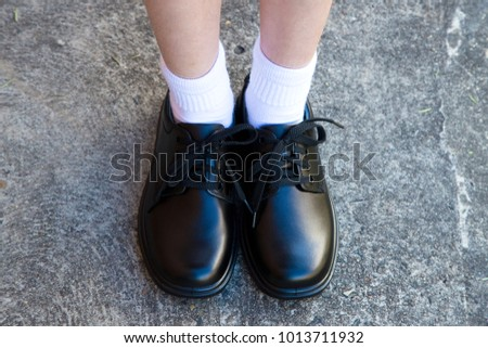 Black leather school shoes worn by a girl student, view of legs with white socks on cement path #1013711932